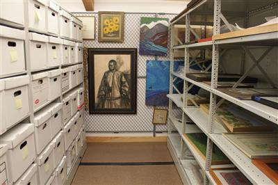 Artwork and filing boxes on wide span shelving and artwork on hanging artrack