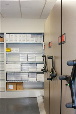 Healthcare supplies on 4-post shelving and mechanical assist mobile high-density shelving