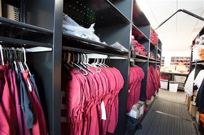 Hanging athletic uniforms on metal shelving at Stanford University